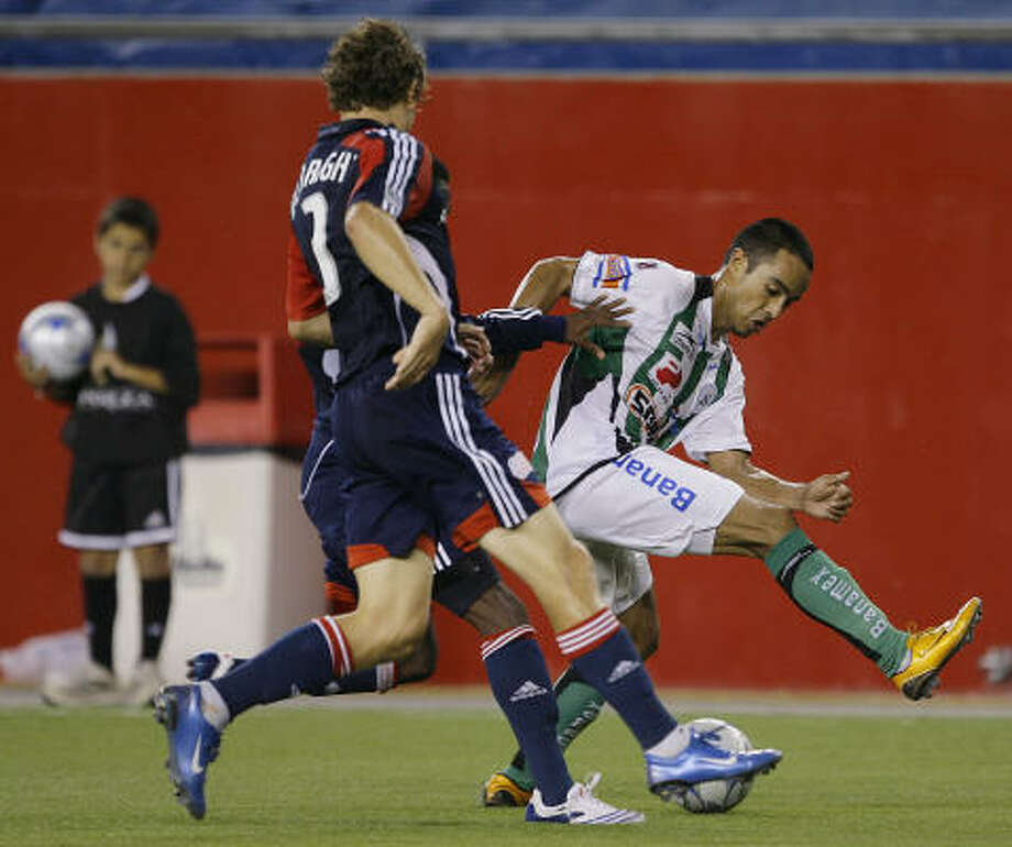 Santos Laguna midfielder Francisco Torres, right, steps over the ball as he dribbles past New England Revolution defender Chris Albright during second half action of their friendly exhibition soccer match. The Revolution won 1-0. Photo: Stephan Savoia, AP