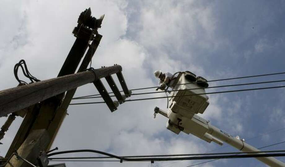 Lineman Shawn Rasmussen works on replacing a pole on Lauder in northeast Houston. Photo: STEVE CAMPBELL, CHRONICLE