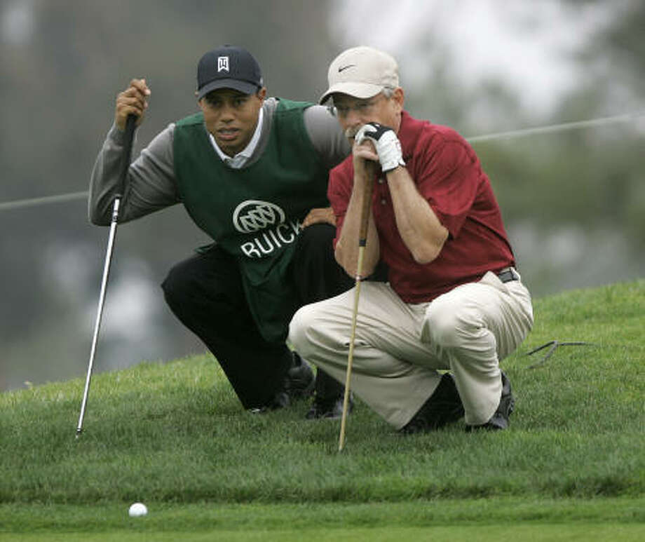 Caddie Tiger Woods lines up a putt with John Abel on the 18th hole at Torrey Pines on Monday. Abel won a contest that entitled him to have Woods caddie. Photo: Lenny Ignelzi, AP