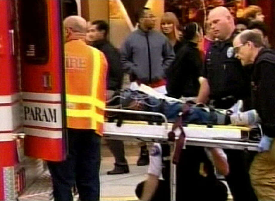 Paramedics load a victim into an ambulance outside the Southcenter Mall in Tukwila, Wash.