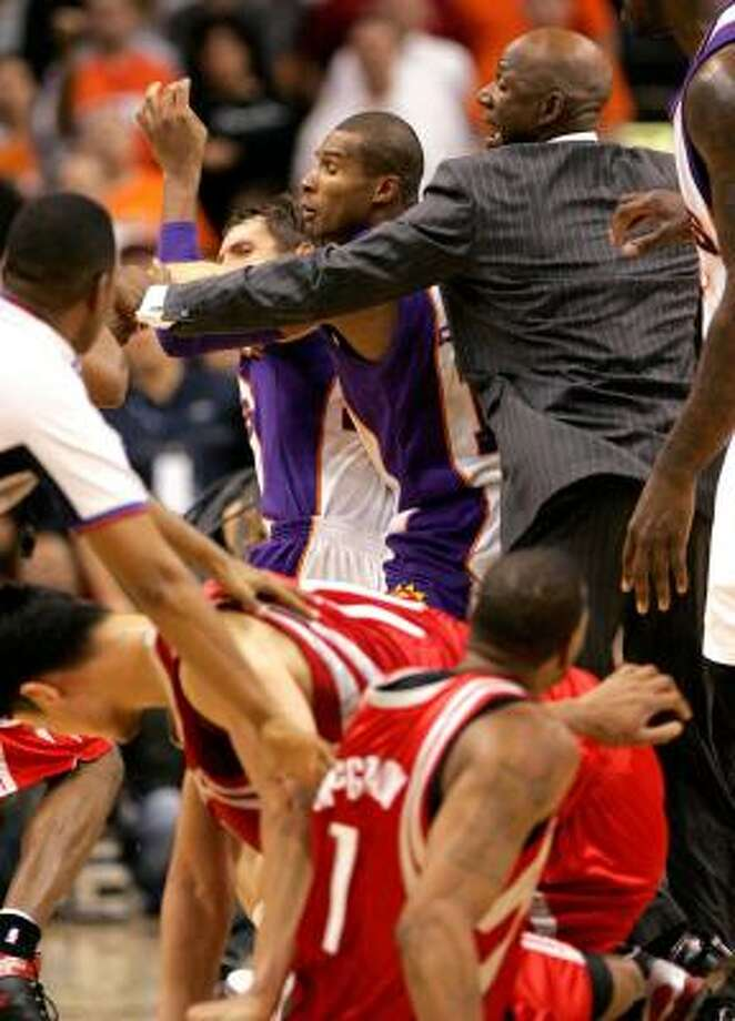 Phoenix coach Terry Porter tries to stop the fight. Photo: Matt York, AP