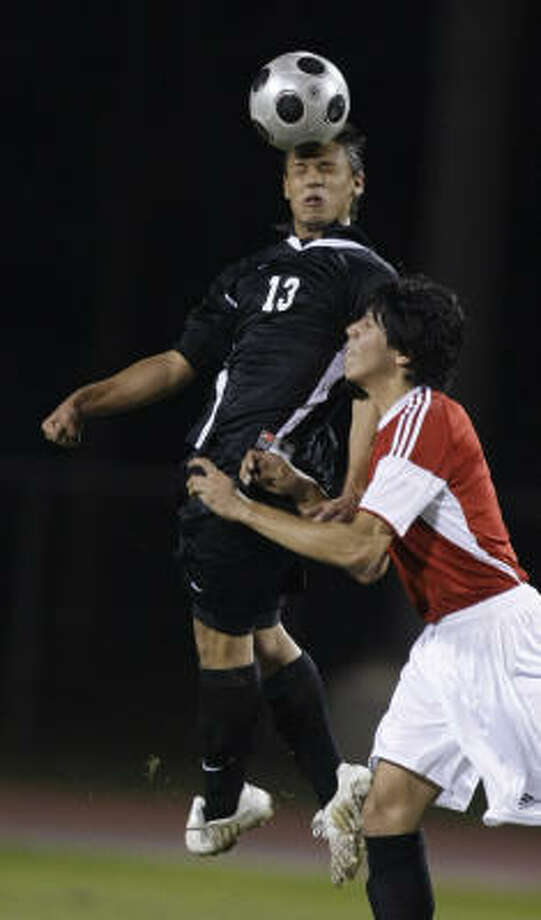 Westside forward Gonzalo De Vitta (13) leaps over Langham Creek defender Miguel Mendoza (7) during the first half of a high school soccer match in the Cypress-Fairbanks Invitational Boys Soccer Tournament on Thursday. Photo: Brett Coomer, Chronicle