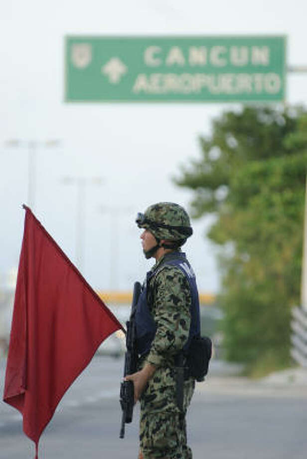A Mexican official monitors a highway checkpoint south of town, searching for drugs and weapons after the general's death. Photo: Keith Dannemiller, For The Chronicle