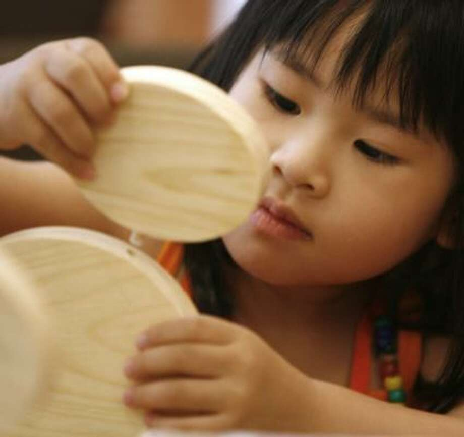 Allison Yue, 3, builds a Mickey Mouse media rack in one of the many Houston Central Library activities on Saturday. The library reopened after a $17 million renovation. Photo: KEVIN FUJII, CHRONICLE