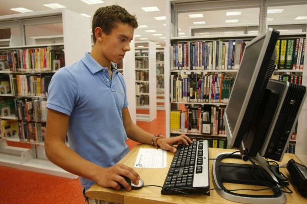 Clevin Cevallos, 14, searches for a book on one of the many upgraded computers at the library.