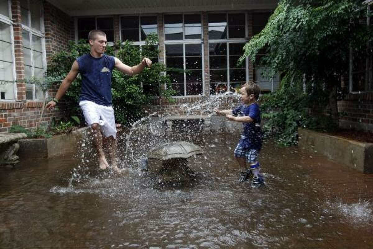 Holden plays with Parker in rainwater outside their home.