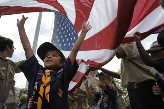 Antonio Ruiz, 7, of Spring, with Cub Scouts Pack 355, joins other scouts as they raise a U.S. garrison flag at the Houston National Cemetery Sunday, May 29, 2011, in Houston. After the garrison flag raising ceremony, the scouts took part in the raising of 300 U.S. flags measuring 5 foot by 10 foot along the cemetery roadways as part of the Avenue of Flags. Both boys and girls scout units took part in this preparation for the Memorial Day Ceremony, to be held at the national cemetery on Monday, May 30, at 9:30 a.m. Photo: Melissa Phillip, Houston Chronicle