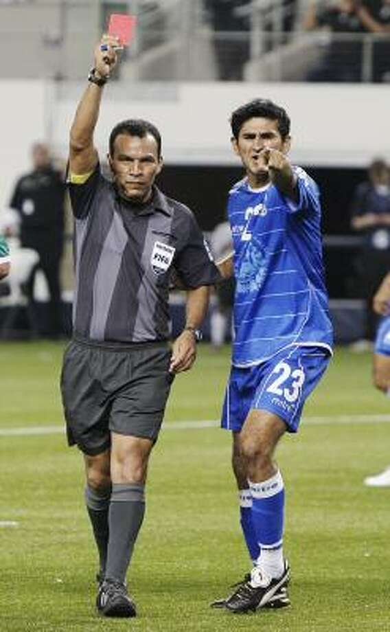 El Salvador defender Luis Alonso Anaya, right, argues with referee Enrico Wijngaarde over a red card issued in the final seconds of the match. Photo: Brandon Wade, Associated Press