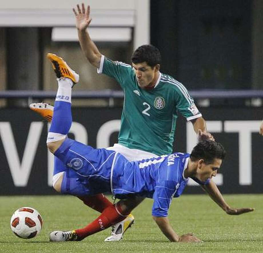 El Salvador striker Rodolfo Zelaya, bottom, is tripped up by Mexico defender Francisco Rodriguez during the second half. Photo: Brandon Wade, Associated Press