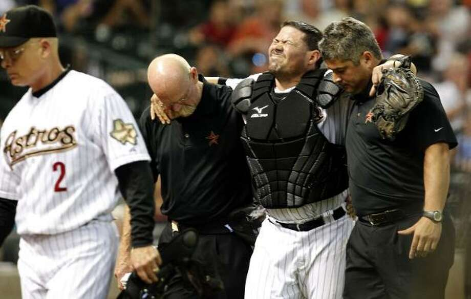 Astros catcher Humberto Quintero is carried off the field by Astros athletic trainer Rex Jones, left, and an unidentified trainer and after a collision at the plate with Arizona's Ryan Roberts. Photo: Johnny Hanson, Chronicle