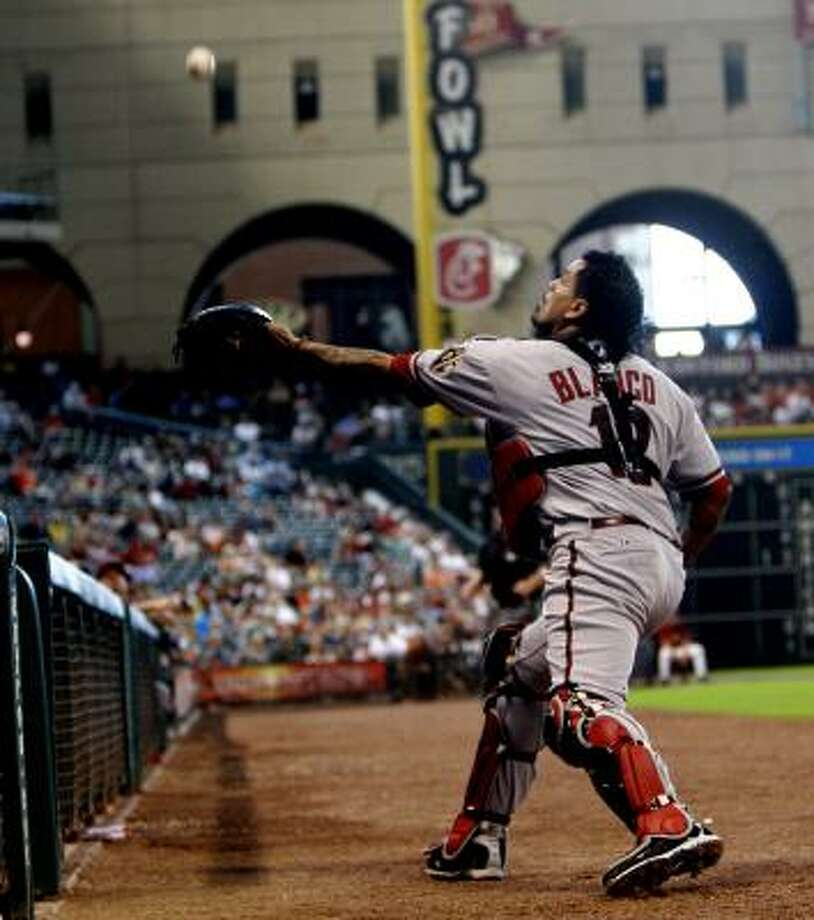 Diamondbacks catcher Henry Blanco makes a catch on a foul ball near the bench. Photo: Bob Levey, Getty