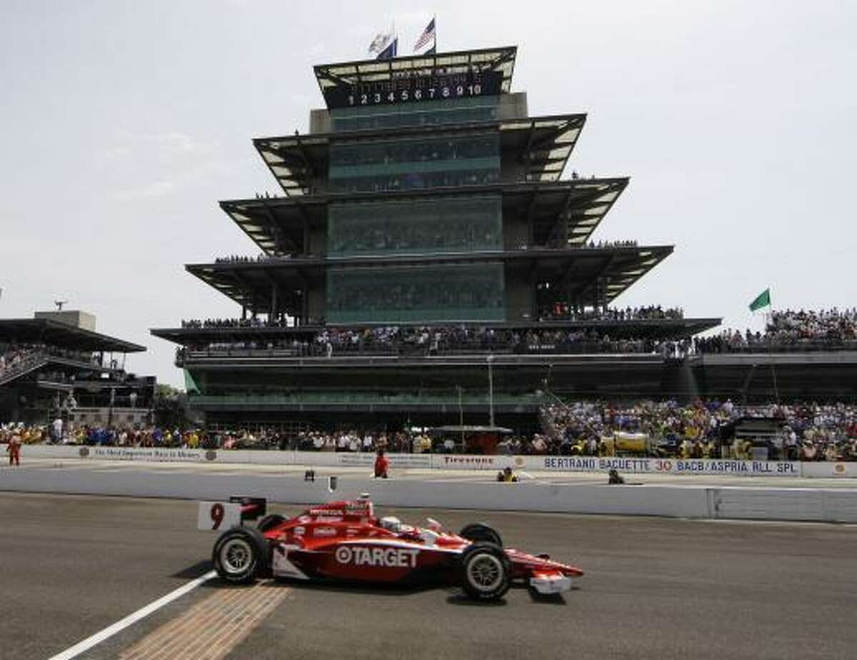 Scott Dixon, of New Zealand, crosses the start-finish line at the start of the Indianapolis 500.