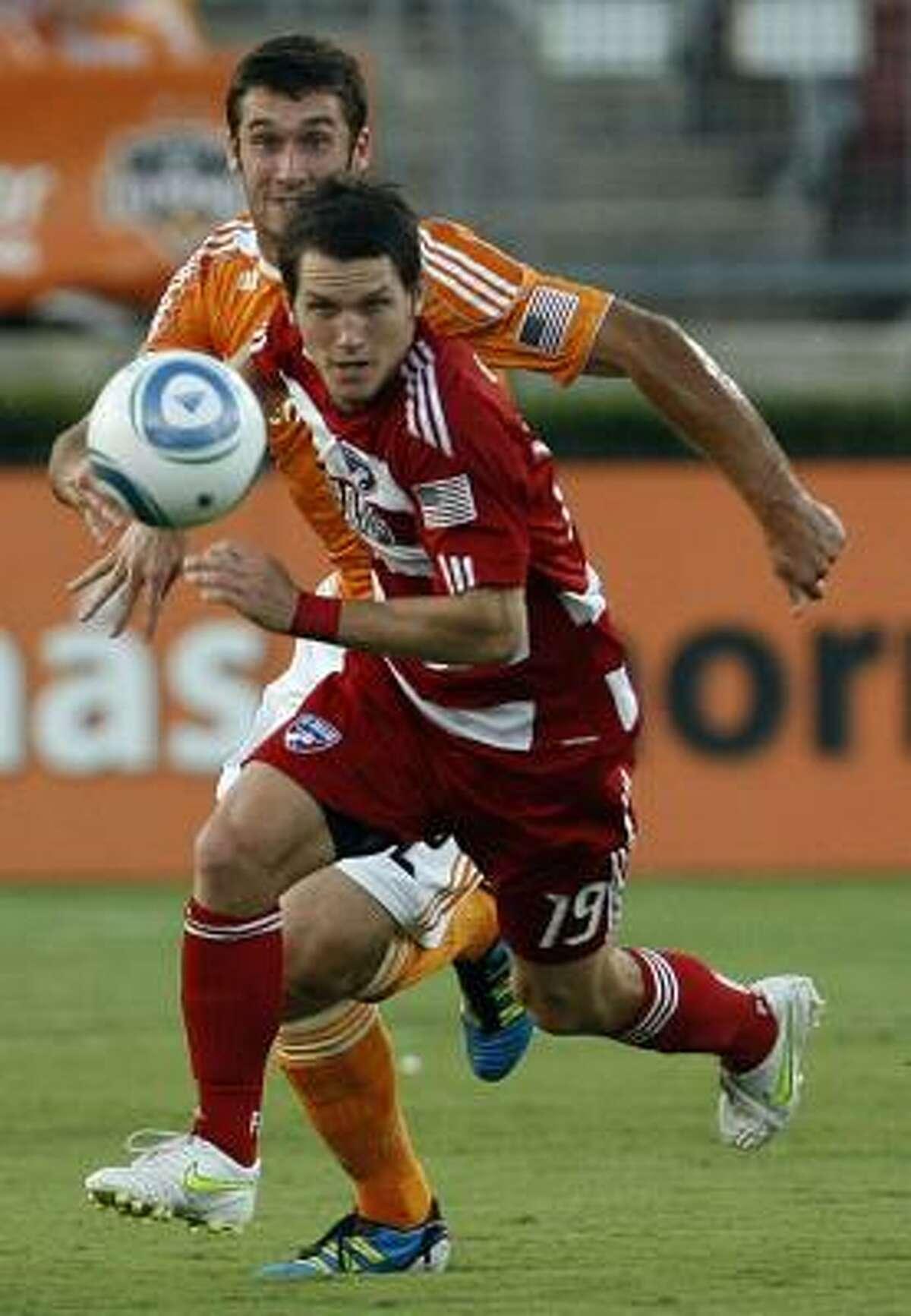 Dynamo forward Will Bruin and FC Dallas defender Zach Loyd battle for the ball.