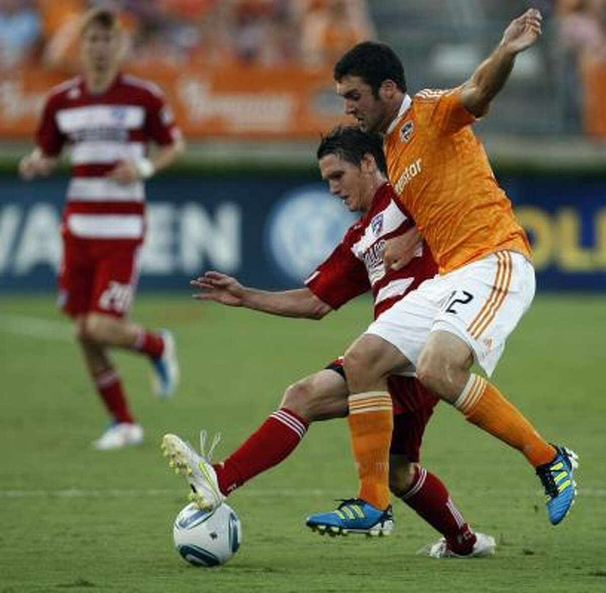 Dynamo forward Will Bruin (12) and FC Dallas defender Zach Loyd (19) battle for the ball.