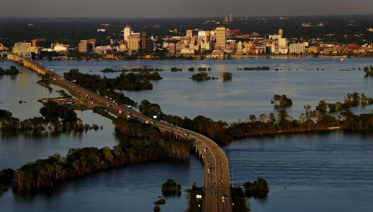 Motorists on Interstate 40 pass over the rising Mississippi River as the sun sets over downtown Memphis, Tenn., on Thursday