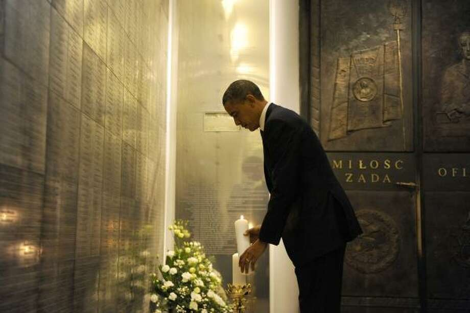 US President Barack Obama lights a candle as he visits the memorial to the victims of the Smolensk plane crash at the Field Cathedral of the Polish Military in Warsaw on May 28, 2011. Obama reassured east European allies that cooperation over missile defence with their Soviet-era master Moscow does not mean NATO will cede partial control to Russia. Photo: JEWEL SAMAD, Getty
