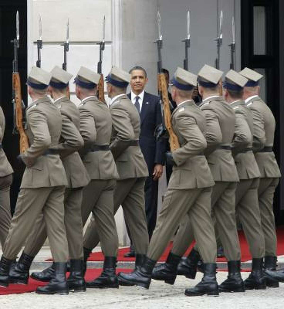 Soldiers march past U.S. President Barack Obama as he takes part in an arrival ceremony at the presidential palace in Warsaw, Poland, Saturday, May 28, 2011. President Barack Obama is meeting with Poland's president as he begins the last day of his European tour. Polish President Bronislaw Komorowski greeted Obama at the presidential palace in a formal ceremony. The two leaders are meeting to discuss democracy and security issues.
