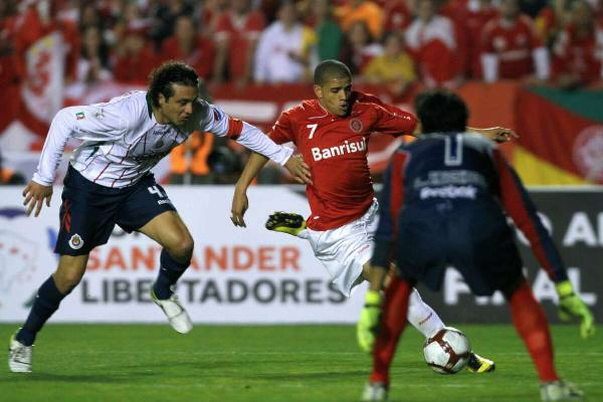 Hector Reynoso (L) of Mexico's Chivas vies for the ball with Taison of Brazilian Internacional during their Libertadores Cup final match at Beira Rio stadium in Porto Alegre, Brazil on August 18, 2010. AFP PHOTO/Jefferson BERNARDES