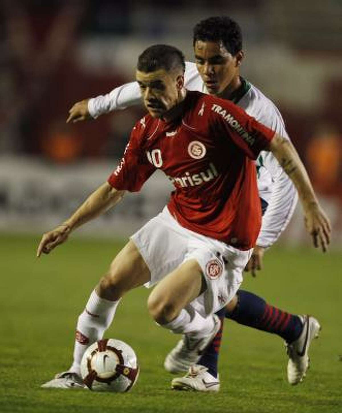 Followed by Mexico's Chivas' Omar Bravo, Brazil's SC Internacional's Andres D'Alessandro, front, plays the ball during the Copa Libertadores final soccer match in Porto Alegre, Brazil, Wednesday, Aug. 18, 2010.