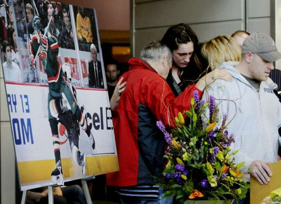 A photo of their son and brother stands at left as Krysten Boogaard(center right), mother Joanne (blonde hair) and father Len (left) console each other as brother Ryan (right) speaks during a memorial at Xcel Arena. Photo: Jim Mone, Associated Press