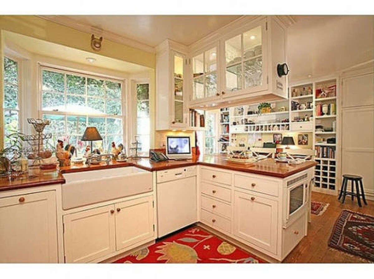 The home's kitchen comes with glass-fronted cabinetry, high-gloss butcher block counter tops, a wide farmhouse-style sink and a three-seat breakfast bar.