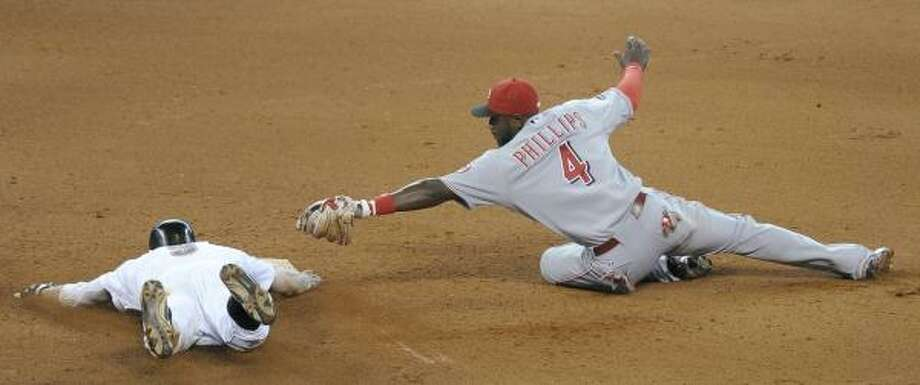 Astros' Hunter Pence, left, slides under the tag of Cincinnati Reds second baseman Brandon Phillips. Photo: Pat Sullivan, Associated Press