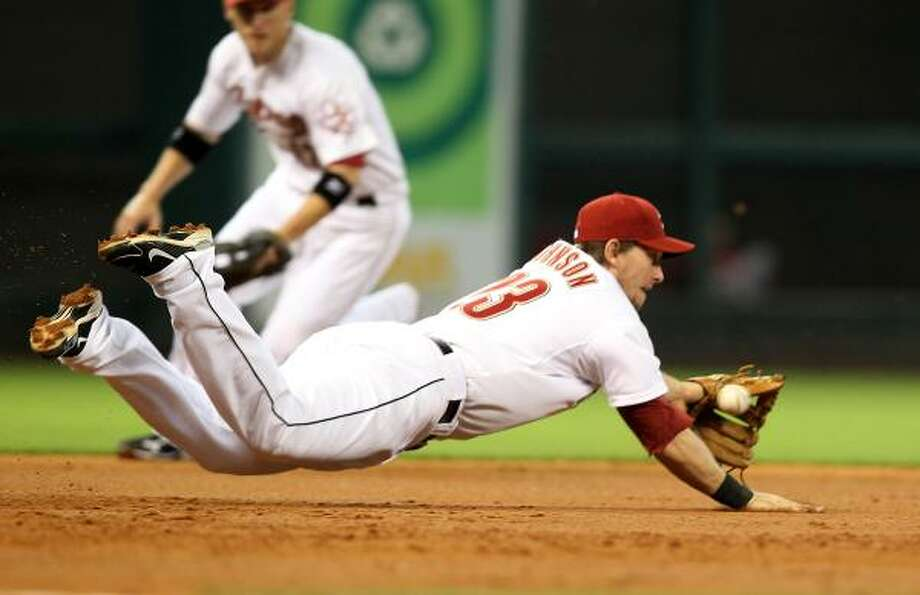 Astros third baseman Chris Johnson dives but can't come up with a ball hit by Drew Stubbs. Photo: George Bridges, McClatchy-Tribune News Service