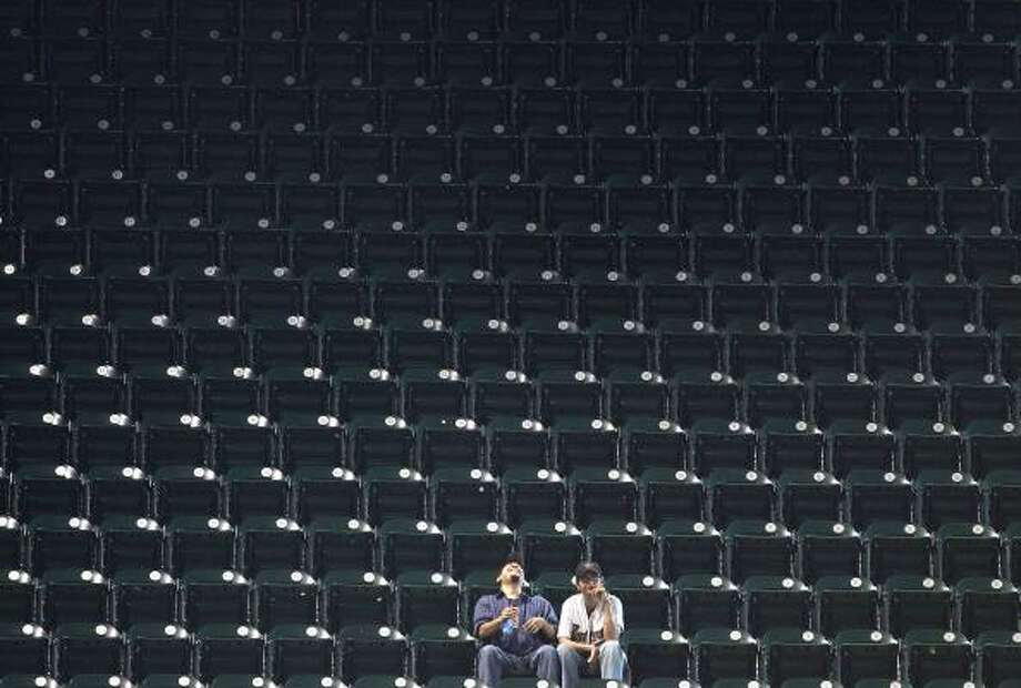 Andrew Villasenor, left, and Katrina Pomaikai, enjoy some peace and quiet during the Astros' win over the Reds. Photo: Nick De La Torre, Chronicle