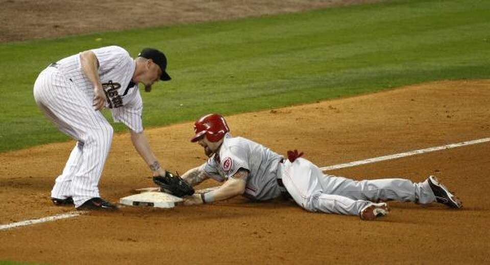 Astros pitcher Brett Myers, left, tags out Cincinnati's Jonny Gomes at third base on a play that was