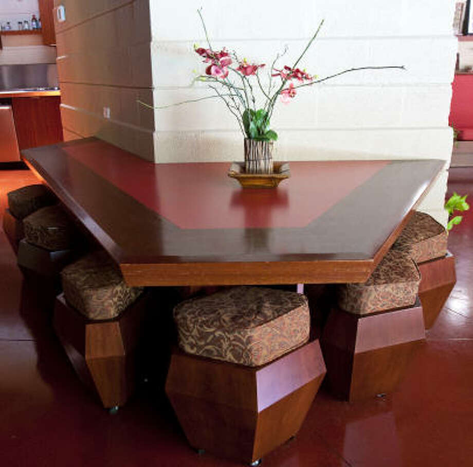He designed it all himself, with most of it anchored to the walls, so the homeowners couldn't even rearrange it. This half-octagon dining room table that attached to a wall has rolling stools so low to the ground that they seem built for children. Photo: Nick De La Torre, Houston Chronicle