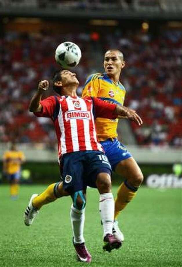 El jugador de Chivas, Alberto Medina, izquierda, cabecea el balón en un partido contra Tigres por el torneo Clausura mexicano el miércoles, 4 de mayo de 2011, en Guadalajara. Photo: Bernardo De Niz, AP