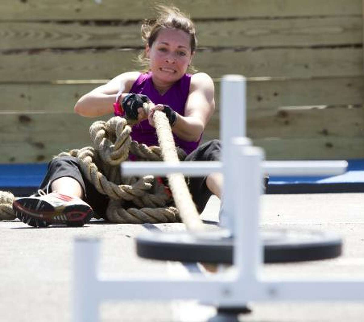 Sasha Kuklis pulls a weighted sled during the Metro Dash race at Reliant Park Saturday, in Houston. More than 1,100 people participated in an intense obstacle course, set up in an area the size of a football field, comprised of 30 obstacles that had participants climbing, crawling, jumping, swinging and scaling their way through the race.