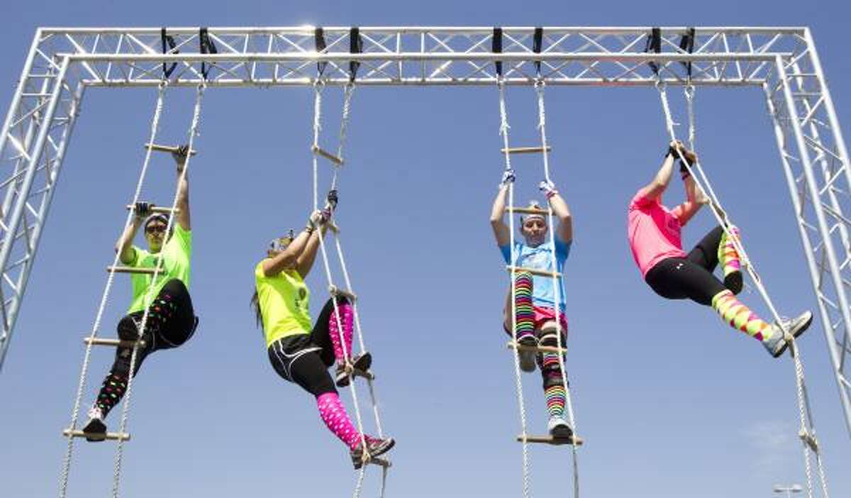 Stephanie Stekiier, left, Elissa Shelton, Sara Anderson and Courtney Schmidt climb rope ladders during the Metro Dash race at Reliant Park Saturday in Houston. More than 1,100 people participated in an intense obstacle course, set up in an area the size of a football field, comprised of 30 obstacles that had participants climbing, crawling, jumping, swinging and scaling their way through the race. Metro Dash was asking for donations to support the Navy SEAL foundation.