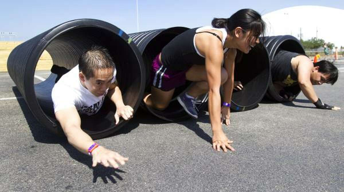 Nam Nguyen, left, Kim Nguyen and Vu Nguyen emerge from plastic tubes during the Metro Dash race at Reliant Park.