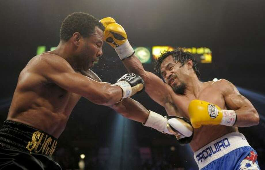 Shane Mosley, left, and Manny Pacquiao exchange punches in the sixth round. Photo: Mark Terrill, Associated Press