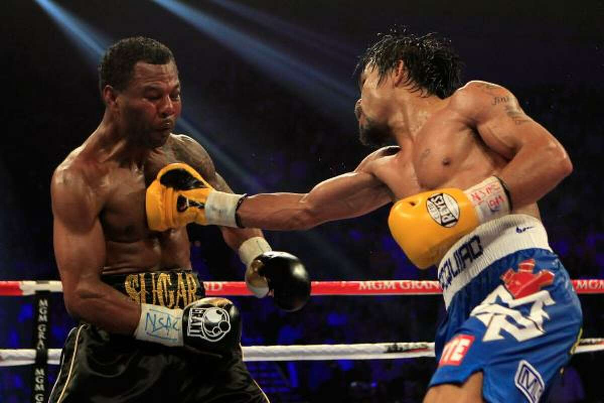 Manny Pacquiao, right, lands a right to the body of Shane Mosley.