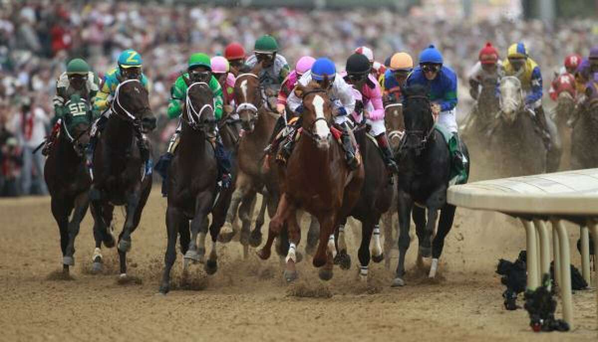 The field rounds the first turn in the 137th Kentucky Derby.