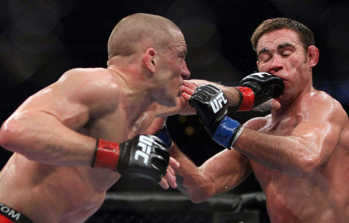 Georges St-Pierre, left, lands a punch on Jake Shields during their welterweight title bout at UFC 129 on Saturday at the Rogers Centre in Toronto. St. Pierre defeated shields in a five-round decision.