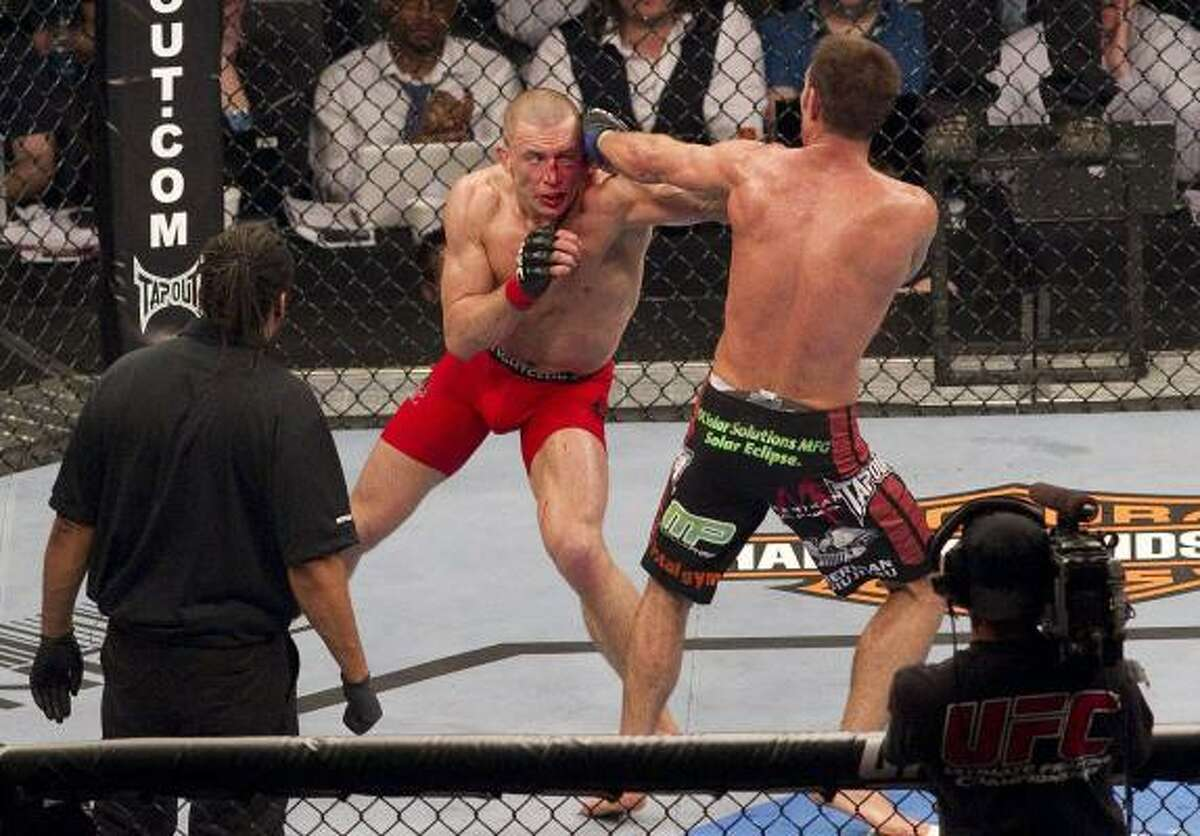 Georges St-Pierre, left, and Jake Shields trade blows during their welterweight championship match.