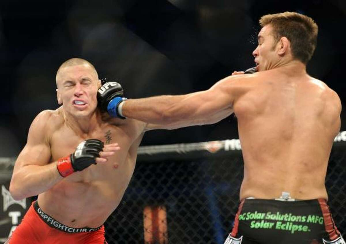 Georges St-Pierre, left, takes a punch from Jake Shields.