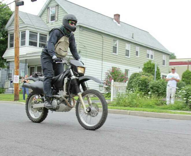 A helmet clad motorcycle rider is captured during filming for