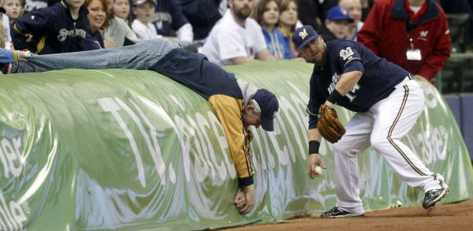 Brewers third baseman Casey McGehee, right, picks up a ball hit by Brett Wallace as a fan reaches for the ball during the first inning. Photo: Morry Gash, AP