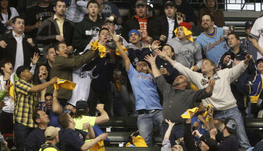 Fans go after a home run ball hit by Carlos Lee during the first inning. Photo: Morry Gash, AP