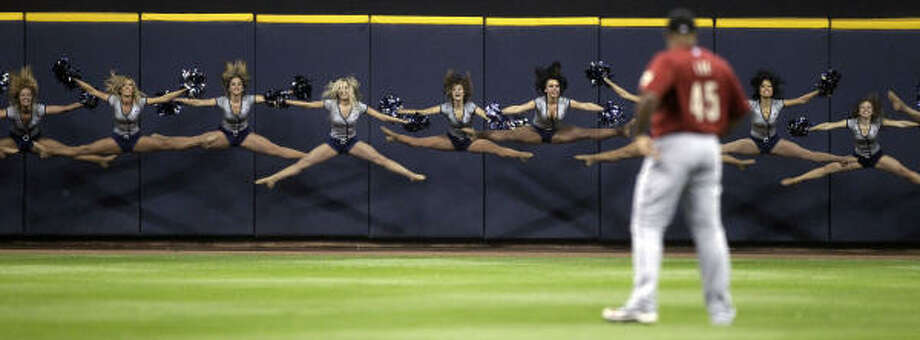 Astros' Carlos Lee watches as cheerleaders perform before a baseball game against the Milwaukee Brewers in Milwaukee. Photo: Morry Gash, AP