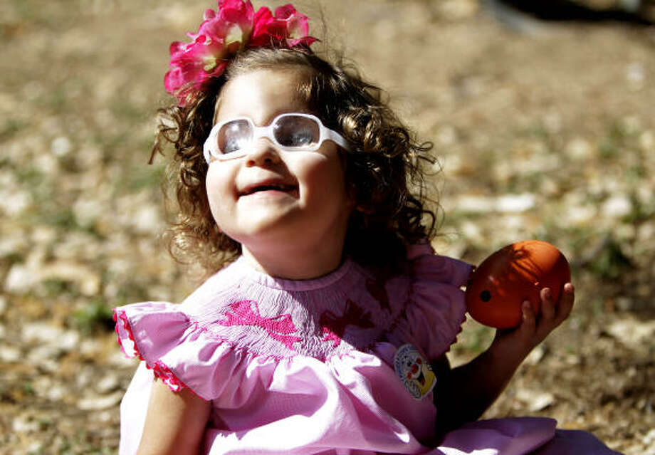 Samantha Folloder, 3, listens to a beeping egg that she gathered at The Lighthouse of Houston Community Services Center during the 29th annual Beeping Easter Egg Hunt for blind and visually impaired children. A tradition since 1982, a non-beeping egg hunt is held for sighted siblings. Photo: Karen Warren, Houston Chronicle