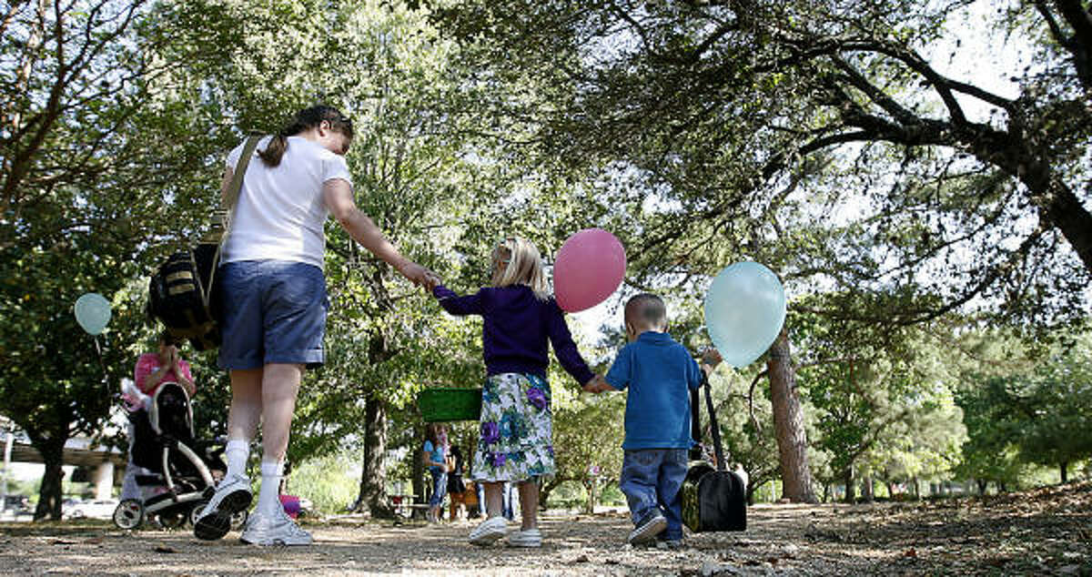 Josie Durant, 4, walks with her mom and brother, Jacob, 2, at The Lighthouse of Houston Community Services Center during the 29th annual Beeping Easter Egg Hunt for blind and visually impaired children.