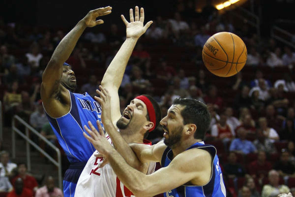 Rockets center Brad Miller (52) loses the ball as Mavericks shooting guard Jason Terry, left, and small forward Peja Stojakovic (16) defend.