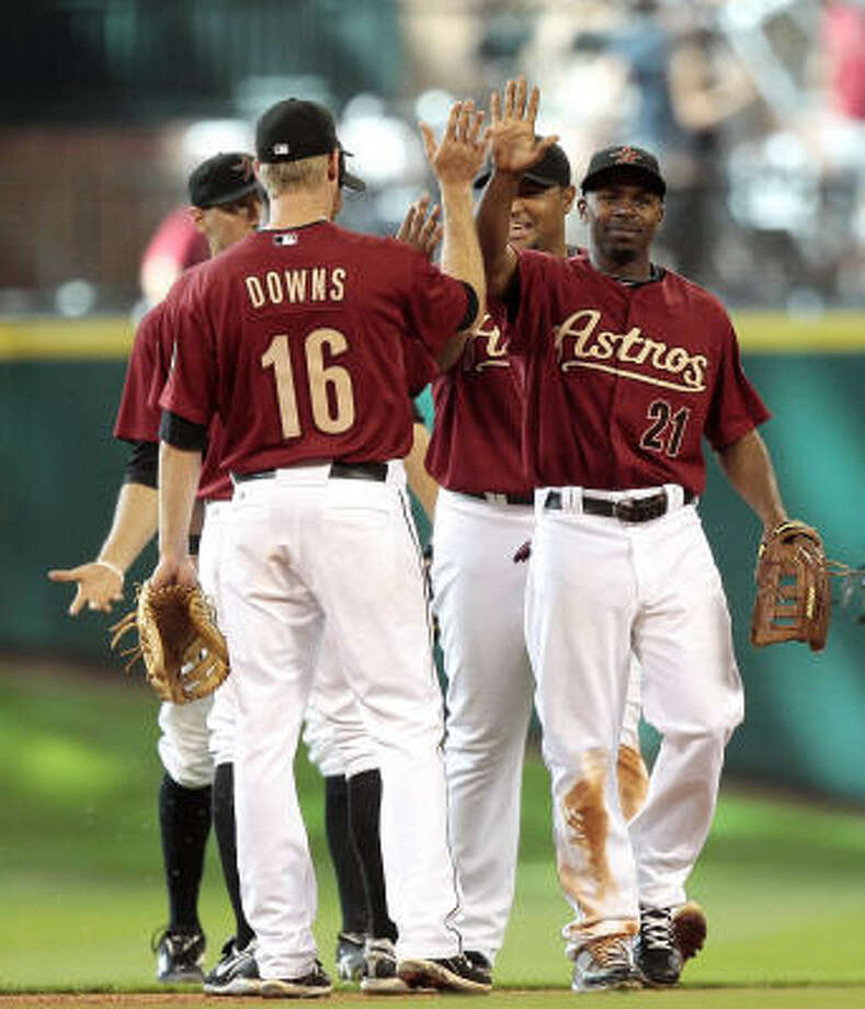 Astros center fielder Michael Bourn (21) high-fives teammate Matt Downs (16) after the final out in the ninth inning. Photo: Bob Levey, AP