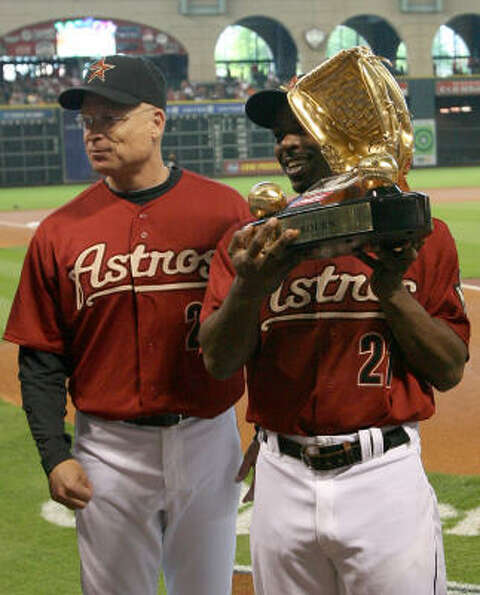 Astros center fielder Michael Bourn holds up his Gold Glove during the pregame ceremony.