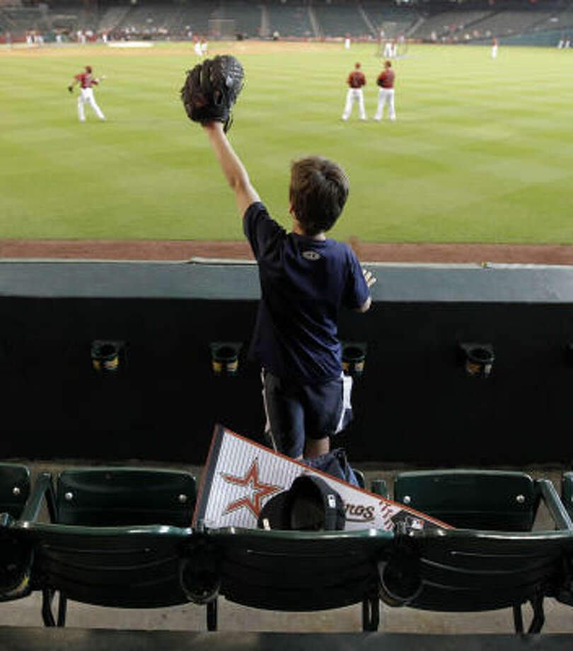 Dylan Shoemake, 8, of Houston, waves his glove as he asks for a ball from his seat in right field. Photo: Karen Warren, Chronicle